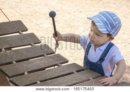 Baby boy playing wooden xylophone. He is at playground