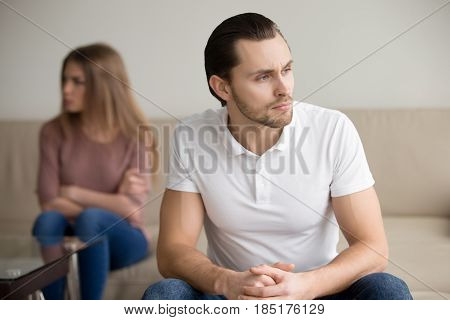 Sad handsome man thinking over problem, taking responsibility, finding compromise, frustrated couple after fight not talking ignoring, stubborn offended girlfriend sitting apart, unsupportive partner