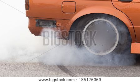 Smoke from under the wheels of the car .