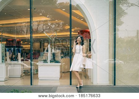 Beautiful Asian Girl With Shopping Bags Listening To Mobile Phone Standing Outside The Mall