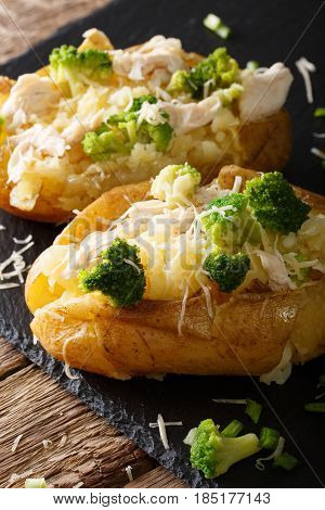 Hearty Hot Baked Potato With Broccoli, Chicken, Onion And Cheese Close-up. Vertical