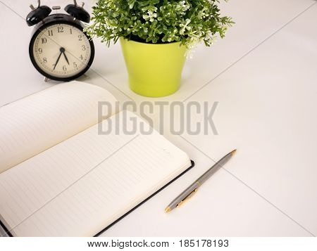 Plain Notebook With A Pen And Clock