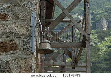 Old signal bell for mountain danger on the wall of rest-house Maliovitza, Rila mountain, Bulgaria