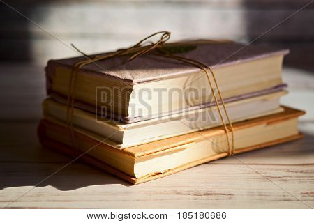 Stack of books, tied with brown twine, on the table near the window with the sun light.