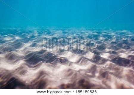 Underwater shoot of an infinite sandy sea bottom with clear blue water and waves on its surface. Pattern of sand in underwater.