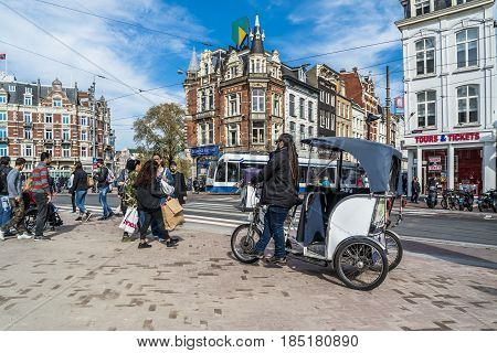 AMSTERDAM , NETHERLANDS - APRIL 31, 2017 : Rickshaw ecotaxi waiting in the streets of Amsterdam