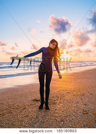 Beautiful young woman surfer girl in wetsuit with surfboard on a beach at sunset or sunrise