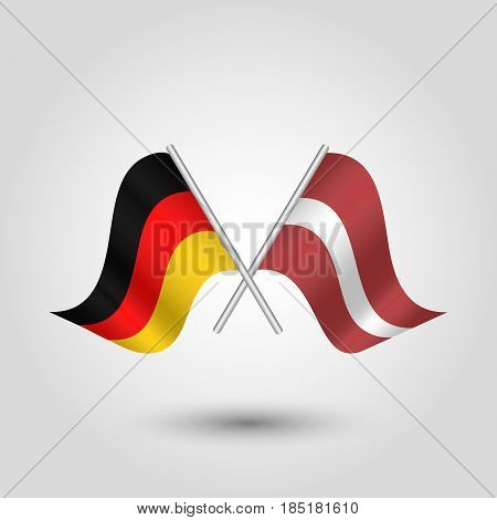 vector two crossed german and latvian flags on silver sticks - symbol of germany and latvia