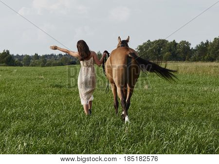 Friends never say goodbye. Long haired brunette woman in elegant dress is walking slowly trough the green meadow with her horse beside . Beautiful natural picturesque view is very authentic.