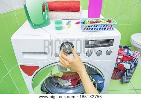 The hand selects the washing mode on the washing machine.