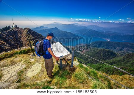 Hiker on Monte Generoso mountain looking at Lugano city San Salvatore mountain and Lugano lake Canton Ticino Switzerland