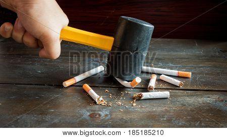 Hand hold hamer smash for destroy many tobaccoes concecpt no smoke forever.