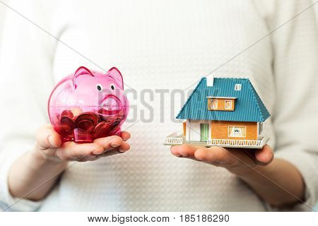 savings for new family house concept - piggy bank and house scale model in hands