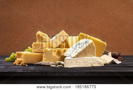 Various types of cheese on black wooden table background. Cheddar, parmesan, emmental, blu cheese. Copy space.