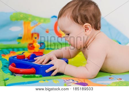 baby playing with educational toys lying in panties