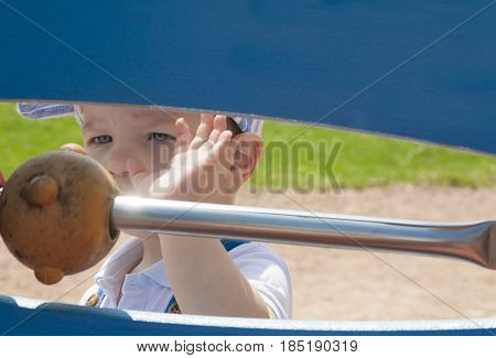 2 year-old boy playing with balls on string. Playground toy