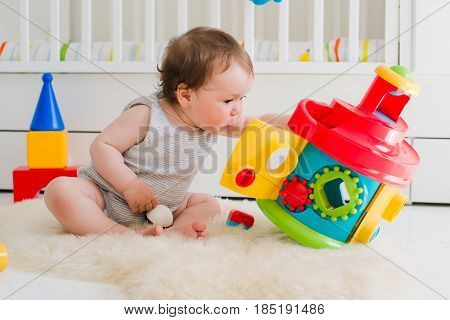 Child 6 months playing sitting on the floor in a developing game