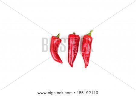Three red jalapeno peppers on white background