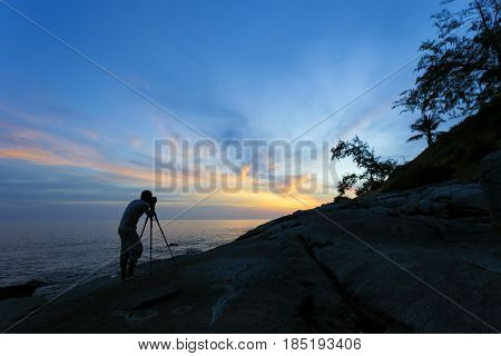 Silhouette of a photographer or traveler using a professional DSLR camera photographer take sunset photo.