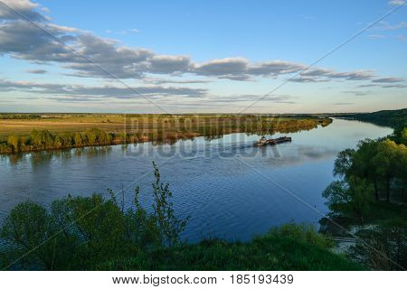 Top view of the turn of the great river and floating in a barge on a may evening