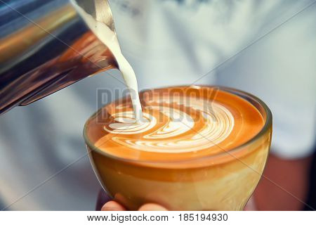 Barista using coffee machine preparing fresh coffee or latte art and pouring into cup at coffee shop and restaurant
