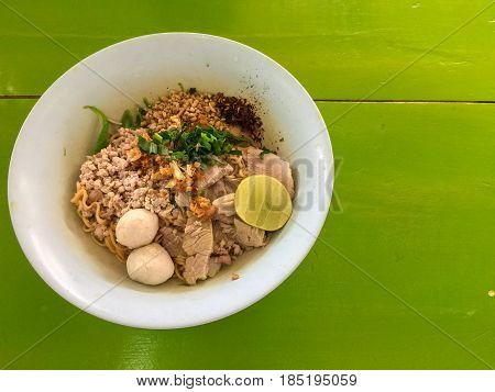 Top view of Thai noodle hot and spicy Tom Yam with lemon and pork on green table.