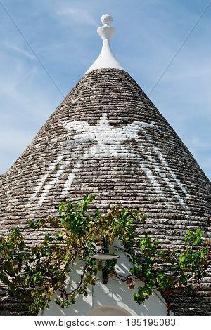 Symbol in the Trullo conical rooftop in Alberobello under a blue sky Puglia Italy