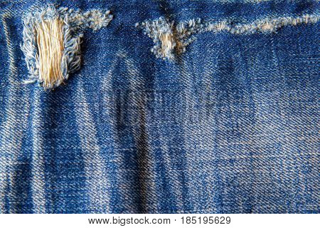 Hole and Threads on Denim Jeans. Ripped Destroyed Torn Blue jeans background. Close up blue jean texture