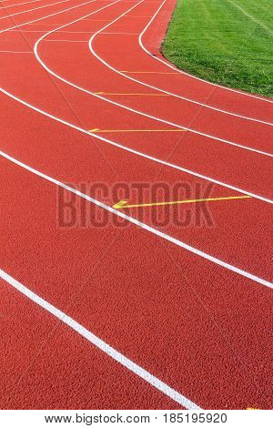 Red running track and white lanes on sport stadium.