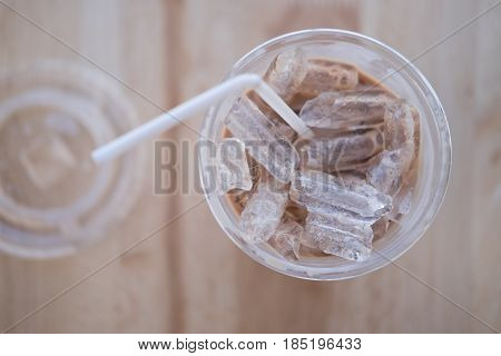 Iced cocoa in plastic cup top view on wood table