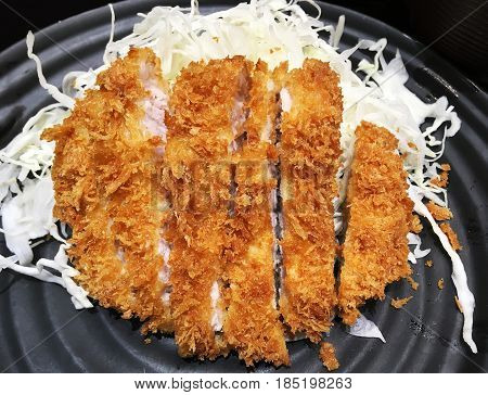 Japanese fried pork name is tonkatsu over sliced white cabbage in black dish top view.