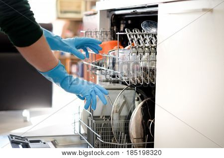 Woman opening the dishwasher in the kitchen main focus on the dishes