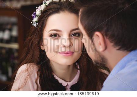 Young beautiful enamored couple sitting at a table in a cafe and going to kiss