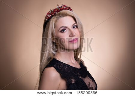 Portrait Of Young Beautiful Woman In Crown Over Beige