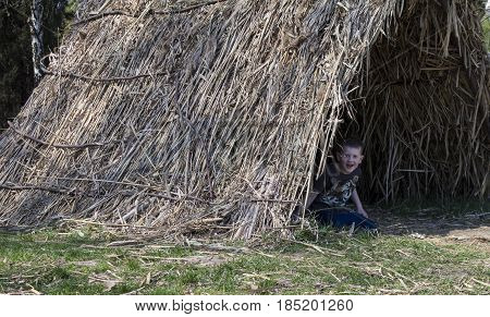 The boy looks out of the straw tent.