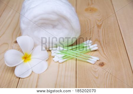 White cotton bud with cotton roll and white flower over wooden table background