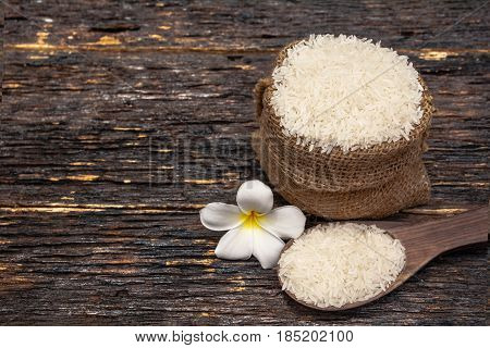 White uncooked rice with White uncooked rice on wooden spoon Thai rice on wooden background