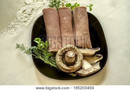 Black plate with slices cookedsausages wrappedwith dillonions and coriander