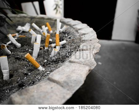 Cigarette butt in the pot. Many cigarette stub in sand ashtray. Close up shot.