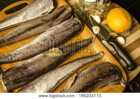 Frozen hake with lemon,salt and bay leaves nearby kitchen knife on wooden board