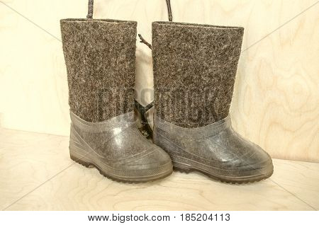 Children's shoes with goat hair with kapron galoshes for a cold winter against the background of plywood