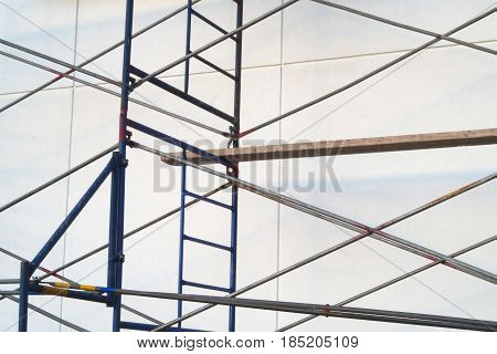 construction site scaffolding metal pipes steel structure white acrylic wall scaffold