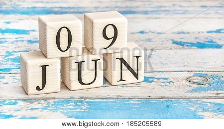 June 9th. Wooden cubes with date of 9 June on old blue wooden background.