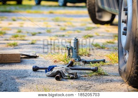 Manual socket wheel wrench and jack lying on ground. Tire car repair objects concept.