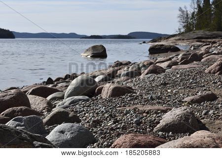 Shore with focus soft rounded granite stones in foreground and sea with islands in background picture from the North of Sweden.