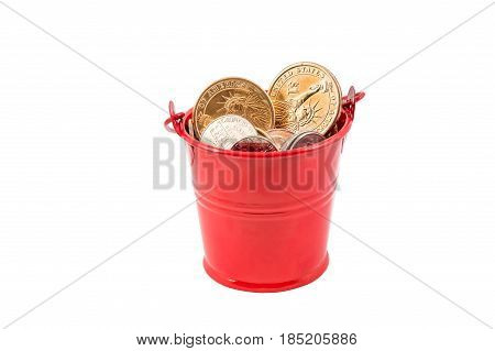 Coins in the red pail. Isolated on white.