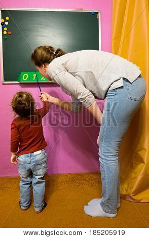 baby girl and the teacher stands at the blackboard in the classroom caused the teacher to the Board and a pointer shows the numbers 0 1 2 3 4