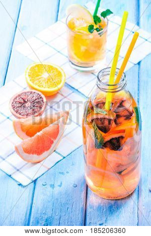 Detox water with various citrus fruit. Bottle and drinking glass with slices of orange, blood orange, lemon and grapefruit. Fresh fruit on the table