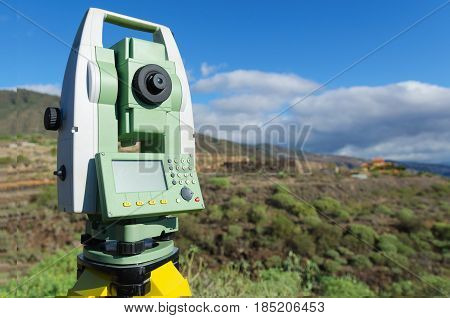 Modern surveyor equipment theodolite or tacheometer used in surveying and building construction for precise measurement. Total station outdoor at construction site. Copy space. poster