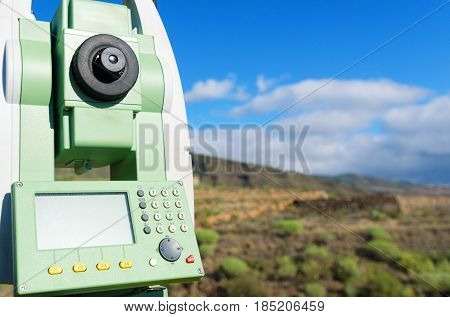 Close up of modern surveyor equipment theodolite or tacheometer used in surveying and building construction for precise measurement. Total station outdoor at construction site. Copy space.